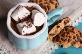 Cups of coffee with marshmallow and cookies on wooden table