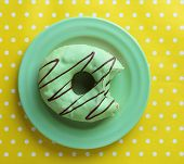 Bitten delicious donut on plate on colorful background