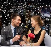 celebration, christmas, holidays and people concept - smiling couple clinking glasses of red wine at restaurant over snowy night city background