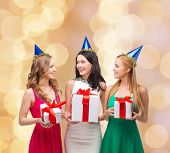 presents, holidays, people and celebration concept - smiling women in party caps with gift boxes over beige lights background