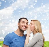 relationships, love, people, information and couple concept - smiling girlfriend telling boyfriend secret over blue sky with snow and grass background