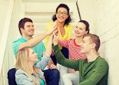 education and happiness concept - smiling students making high five gesture sitting on staircase