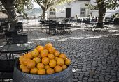 oranges to offer on a square with outdoor seating