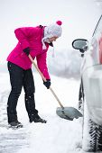 picture of shovel  - Woman  shoveling and removing snow from his car during a snowing - JPG