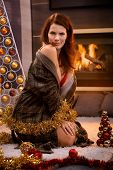 Sexy woman posing in bra and dressing gown at christmas tree and decoration in cosy living room with fireplace.
