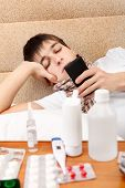 stock photo of home remedy  - Sick Teenager with Cellphone on the Sofa at the Home with Pills on foreground - JPG