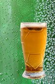 picture of ice crystal  - Froth beer glass taken closeup on ice crystals and drips green background - JPG