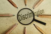 stock photo of racial discrimination  - Word Discrimination under a magnifier as a conceptual image about the phenomena - JPG