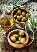 image of olive branch  - Fresh olives and olive oil on rustic wooden background - JPG