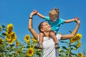 image of mums  - Small son with mum among sunflowers against blue sky - JPG