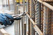 stock photo of reinforcing  - Construction Site Worker is preparing reinforcement cage for concrete column using steel wire and pincers - JPG