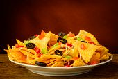 pic of nachos  - nachos tortilla chips with cheese olives and chili peppers on a plate - JPG