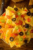 image of nachos  - nachos closeup with cheese olives and chili peppers on a plate - JPG