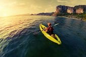 picture of kayak  - Lady with backpack paddling the kayak in the calm bay at sunset - JPG