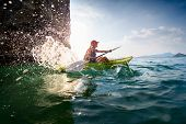 stock photo of kayak  - Young lady paddling hard the sea kayak with lots of splashes - JPG