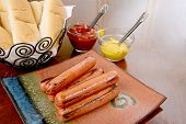 stock photo of condiment  - Grilled hot dogs on a stacked on a plate ready to serve with condiments ketchup and mustard and buns - JPG