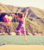 picture of dock a lake  -  a carefree young woman jumping on a dock with balloons toned with a retro vintage instagram filter effect app or action  - JPG