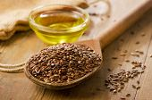 stock photo of spooning  - Brown flax seeds on a spoon and flaxseed oil - JPG
