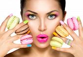 picture of colore  - Beauty fashion model girl with colourful makeup and manicure taking colorful macaroons - JPG