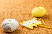 picture of knitting  - roll of white and yellow soft knitting yarn knitting needle on cork background - JPG