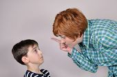 stock photo of scared  - Woman scolding and pointing her index finger at the scared young boy - JPG