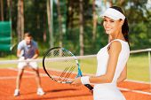 stock photo of ball cap  - Beautiful young woman holding tennis racket and looking over shoulder with smile while man in sports clothing standing in the background - JPG