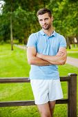 picture of toothless smile  - Handsome young man keeping arms crossed and smiling while standing outdoors and leaning at the fence - JPG