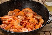 stock photo of tiger prawn  - black pan with red cooked prawns close up on wooden table - JPG