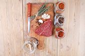 picture of flesh  - fresh raw beef meat fillet flesh with peppercorn and thyme ready to grill on wood figured old style board  over table with spices in glass - JPG