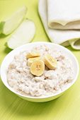 picture of porridge  - Oatmeal porridge with bananas slices in white bowl on green table - JPG