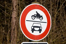 stock photo of bans  - road sign ban of cars and motorcycles in the wood in germany. Ban on motorcycles with sidecars; mopeds and scooters; as well as for cars and other track vehicles.