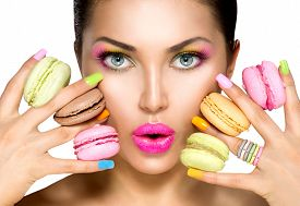 foto of lipstick  - Beauty fashion model girl with colourful makeup and manicure taking colorful macaroons - JPG