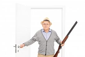 picture of shotgun  - Angry senior man with hat holding a shotgun and walking through an open door isolated on white background - JPG