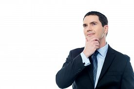 stock photo of thinkers pose  - Thoughtful businessman with hand on chin over white - JPG