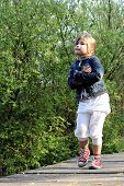 image of hughes  - Young blond girl with tenderness expression walking on wooden bridge outdoor - JPG