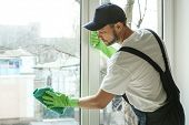 Young man cleaning window in office poster