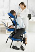 Masseur giving neck massage to businessman in office.?