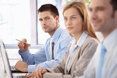 Handsome, confident businessman sitting at meeting room, having training with colleagues.?