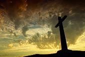 Cruz silueta con la puesta del sol como fondo
