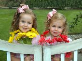 foto of hair bow  - Beautiful young girls are dressed identically with light pink dresses and hairbows - JPG