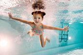 Adorable Kid Swimming Underwater In Blue Water In Swimming Pool poster
