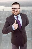 image of feeling stupid  - young silly business man going thumb up - JPG