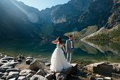 Groom And Bride In Beautiful White Wedding Dress Standing On The Stony Shore Of The Morskie Oko Lake poster