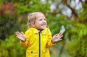 Kids Play In Autumn Rain. Child On Rainy Day. poster