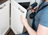 A Professional Handyman Assembling Kitchen Door Cabinet. poster
