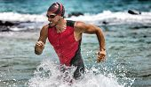 Triathlon swimming man running out of water during ironman race. Male triathlete finishing swim time poster
