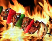 foto of flame-grilled  - image of pork barbeque on flaming hot background - JPG