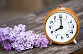 Daylight Savings, Spring Forward Concept - Orange Alarm Clock And Purple Lilac Flowers poster