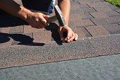 Roofing Construction. Roofer Installing Asphalt Shingles On House Construction Roof Corner With Hamm poster