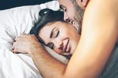 Happy Romantic Couple Having A Tender Moment In The Bed - Young Passionate Lover Waking Up In The Mo poster